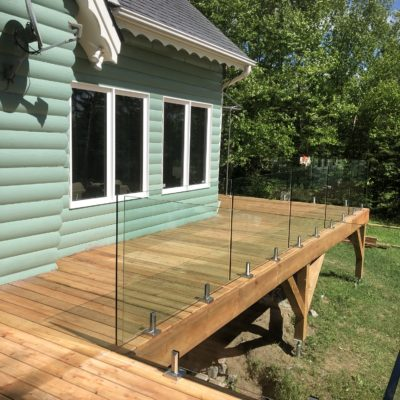 White cedar deck and glass railing in Val-des-Lacs